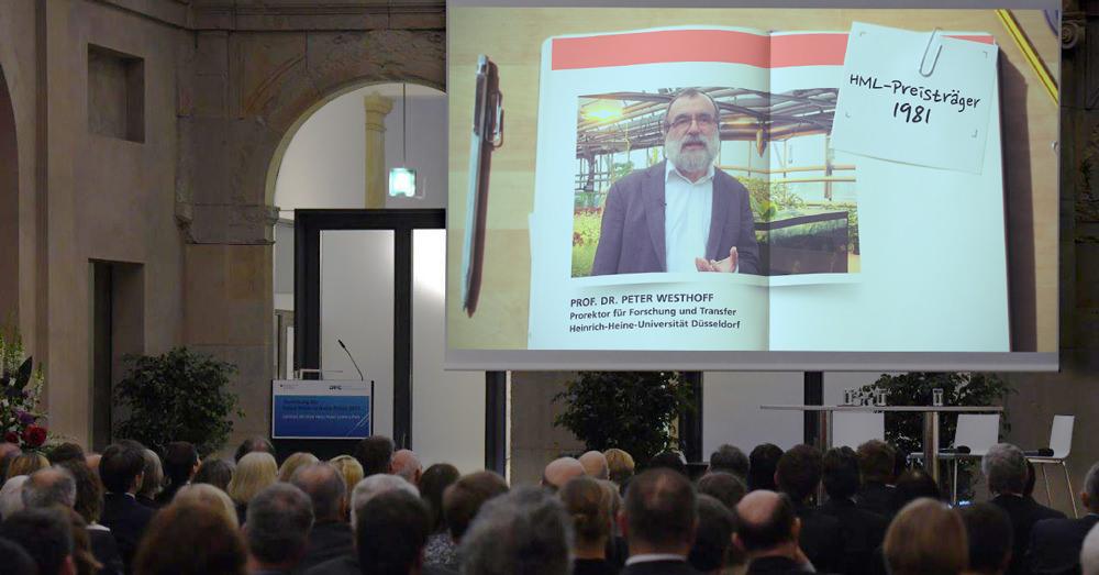 Foto vom Jubiläums-Festakt: Publikum schaut auf Leinwand